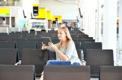 Fille avec un comprimé dans l'aéroport Photo libre de droits