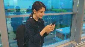 Fille avec un concept d'a?roport de vols d'avion de sac ? dos l'adolescente de fille avec un smartphone regarde la fen?tre banque de vidéos