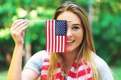 Fille avec un drapeau américain sur le quatrième de juillet Photo stock