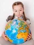 Fille avec un globe sur le fond blanc Photographie stock libre de droits