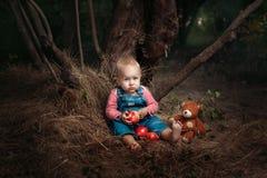 Fille avec un jouet dans le bois Photos stock