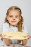 Fille avec un léger sourire tenant une croûte de pizza d'un plat Image stock