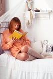 Fille avec un livre jaune de maison Jeune femme sur le lit avec un livre Fille avec le livre La fille lit Images stock