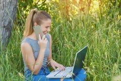 Fille avec un ordinateur portable parlant au téléphone en nature image stock