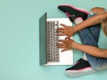 Fille avec un ordinateur portable sur le plancher bleu La vue à partir du dessus image stock