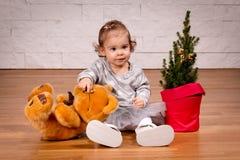 Fille avec un ours de nounours avec l'arbre de Noël Photographie stock libre de droits