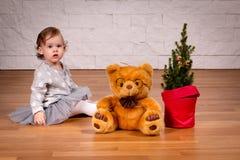 Fille avec un ours de nounours avec l'arbre de Noël Images stock