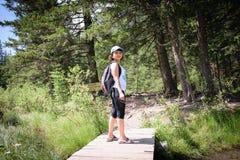 Fille avec un sac à dos dans la forêt Photo stock