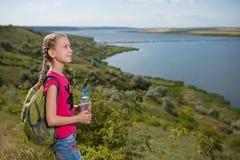Fille avec un sac à dos se tenant sur le fond du lac et de l'eau potable  Photographie stock