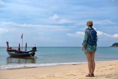 Fille avec un sac à dos sur la plage, bateau thaïlandais traditionnel Photos stock