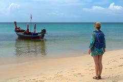 Fille avec un sac à dos sur la plage, bateau thaïlandais traditionnel Photographie stock libre de droits