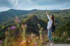 Fille avec un sac à dos sur le fond des montagnes de forêt Photos libres de droits