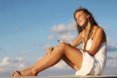 Fille avec un smartphone se reposant sur la plage Images stock