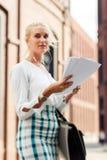 Fille avec un téléphone et un papier dans des mains Images libres de droits