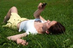 Fille avec un téléphone portable s'étendant sur une herbe Images libres de droits