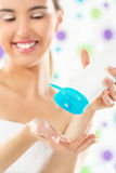 Fille avec un tube de lotion de corps Images stock