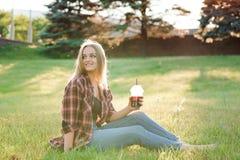 Fille avec un verre de jus sur un pré vert photos stock