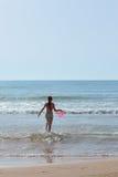 Fille avec une boule rouge en mer parmi les vagues Image stock