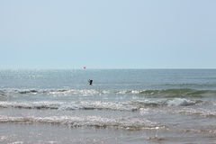 Fille avec une boule rouge en mer parmi les vagues Images libres de droits