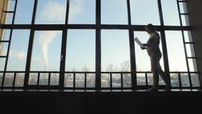 Fille avec une feuille de papier à la fenêtre banque de vidéos