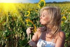 Fille avec une fleur dans le tournesol Photographie stock libre de droits