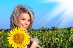 Fille avec une fleur dans le tournesol Photos libres de droits