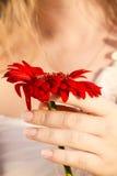 Fille avec une fleur dans sa main sous un soleil doux de coucher du soleil Image stock