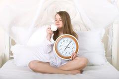 Fille avec l'horloge et la tasse à 5h30 du matin Images stock