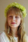 Fille avec une guirlande verte sur sa tête Images stock