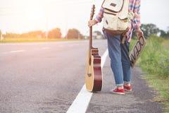 fille avec une guitare faisant de l'auto-stop Images stock