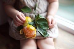 Fille avec une mandarine Photo stock