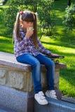 Fille avec une pomme dans des jeans Photographie stock