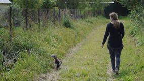 Fille avec une promenade de chat sur un chemin de terre Photos stock