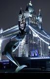Fille avec une statue de dauphin Photos libres de droits