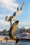 Fille avec une statue de dauphin photo libre de droits