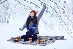 Fille avec une tasse de boisson chaude dans la forêt d'hiver images libres de droits