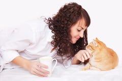 Fille avec une tasse de café et de chat rouge Images stock