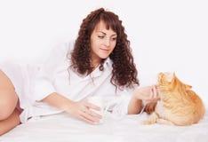Fille avec une tasse de café et de chat rouge Image libre de droits
