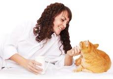 Fille avec une tasse de café et de son chat dans le lit Photos libres de droits