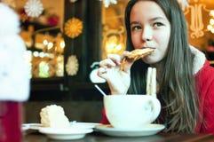 Fille avec une tasse de thé dans un café de Noël Images stock