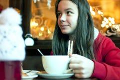Fille avec une tasse de thé dans un café de Noël Photographie stock libre de droits
