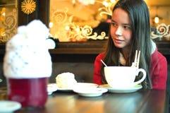 Fille avec une tasse de thé dans un café regardant loin Photo stock