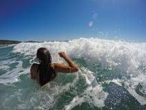 Fille ayant l'amusement dans de grandes vagues de mer Images stock