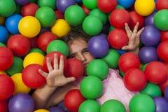 Fille ayant l'amusement jouant dans une piscine en plastique colorée de boule Photo stock