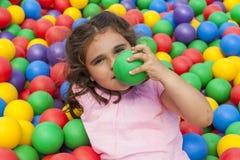 Fille ayant l'amusement jouant dans une piscine en plastique colorée de boule Photographie stock libre de droits