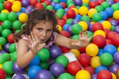 Fille ayant l'amusement jouant dans une piscine en plastique colorée de boule Photos libres de droits