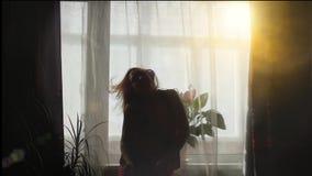 Fille ayant la danse d'amusement à la fenêtre dans la lumière du soleil clips vidéos