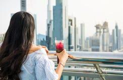 Fille ayant une boisson avec la vue de Dubaï images stock
