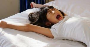 Fille baîllant sur le lit dans la chambre à coucher 4k banque de vidéos