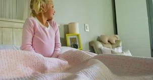 Fille baîllant sur le lit dans la chambre à coucher 4k clips vidéos